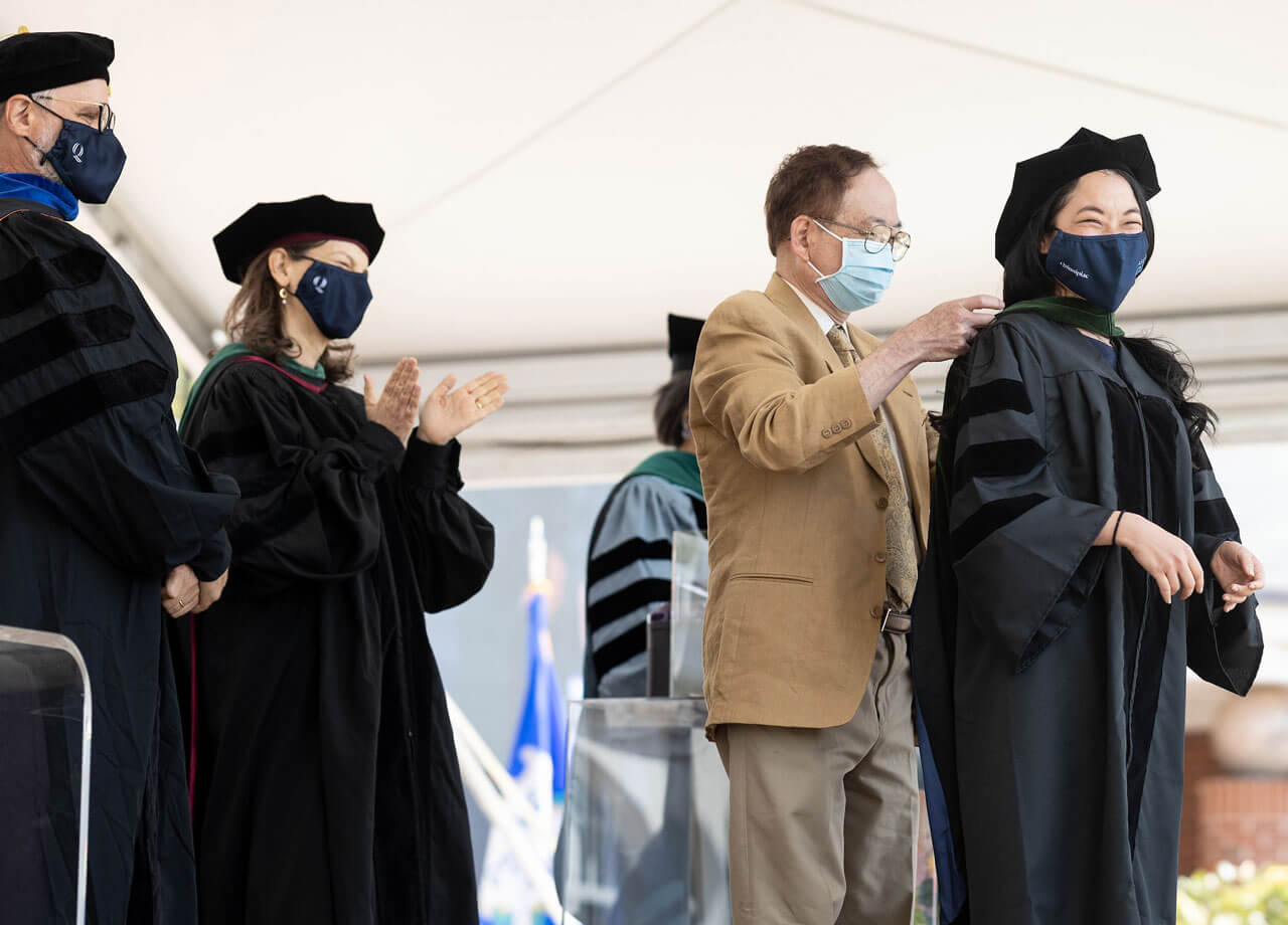 A graduate receives her doctoral hood from her father during Commencement