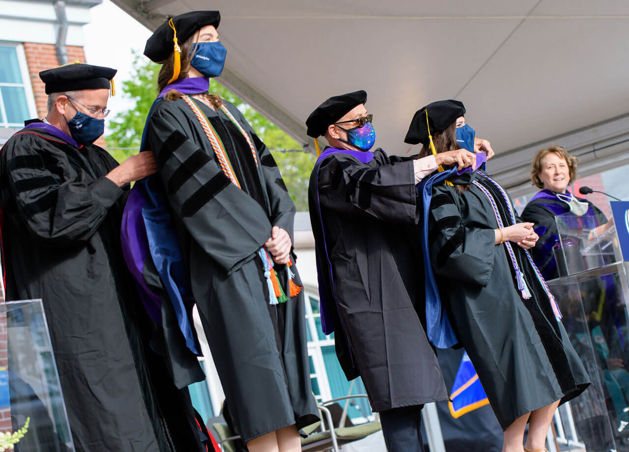 Faculty members drape doctoral hoods on two new graduates
